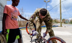A British Army engineer helps to fix a local boy's bicycle on the Island of Anguilla, September 2017