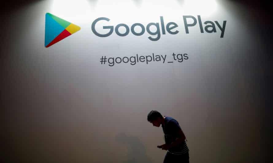 A man walking under a logo of Google Play
