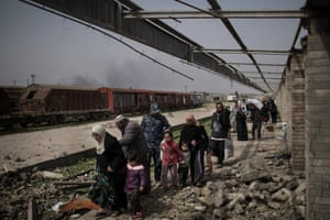 Civilians flee through a destroyed train station during fighting between Iraqi security forces and Islamic State militants, on the western side of Mosul