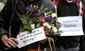 People hold flowers and signs outside EU headquarters in Brussels during a vigil for the journalist Daphne Caruana Galizia.