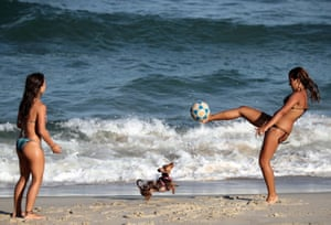 Women play football on Rio de Janeiro's Diabo beach. People in the coastal Brazilian state have been warned to avoid beaches, among a range of measures to curb the spread of Covid-19