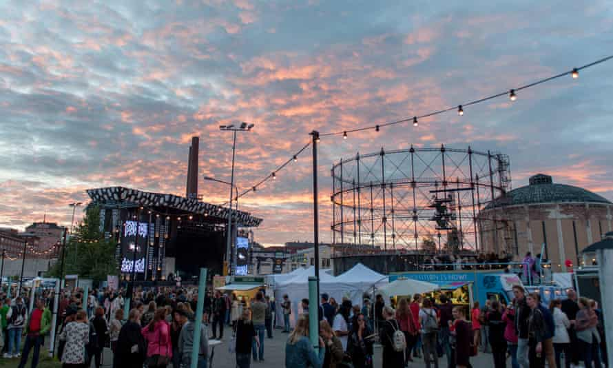 At dusk, crowds begin to gather at the stage for a performance at the Flow Festival in Finland.
