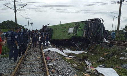 Rescuers stand by a damaged train after a deadly crash with a bus two about 80km east of Bangkok