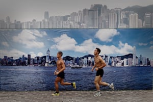 Two men run past a billboard in Hong Kong