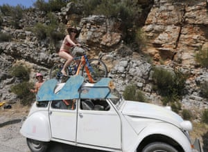 A spectator seems to be enjoying herself on top of a Citroen 2CV as she waits for the pack to pass during the seventeenth stage between Digne-les-Bains and Pra Loup