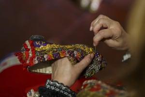Dori Ropero 50, fixes a shoe of the traditional costume of 'Lagarterana' before the start of the Corpus Christi procession