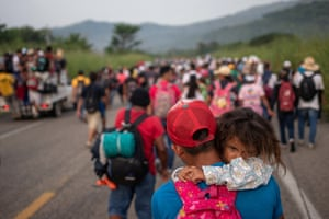 A man from Honduras carries his daughter Allison, 4, as he walks amid a caravan of thousands of migrants from Central America en route to the United States in the outskirts of Arriaga, Mexico