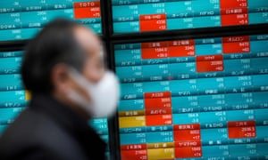 A man wearing a face mask walks past a stock indicator displaying share prices in Tokyo.