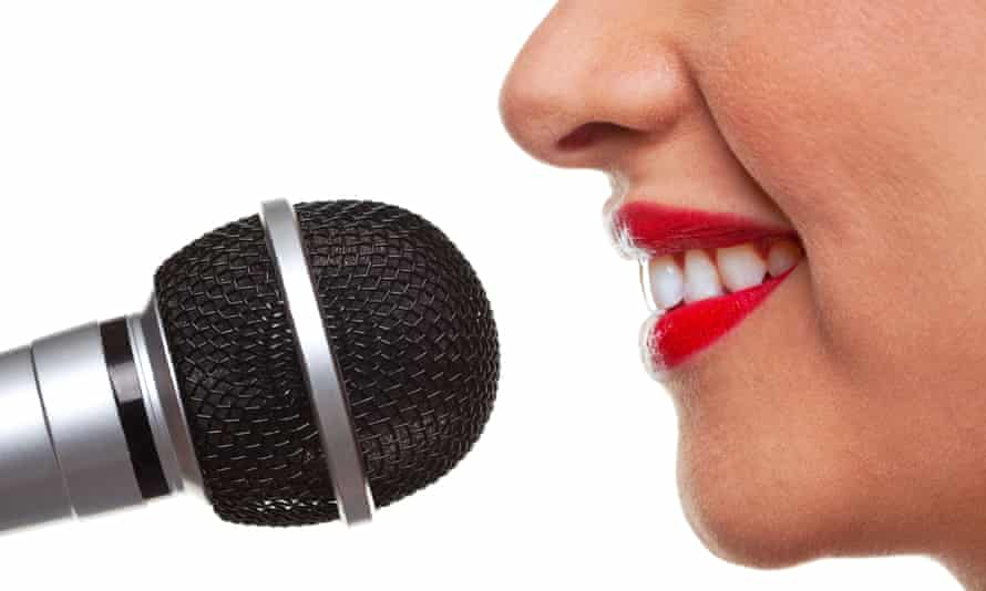 Close up of a woman using a microphone, isolated on a white background.