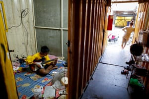 Cambodian Pap Li, a 22-year-old construction worker, plays the guitar inside his unit