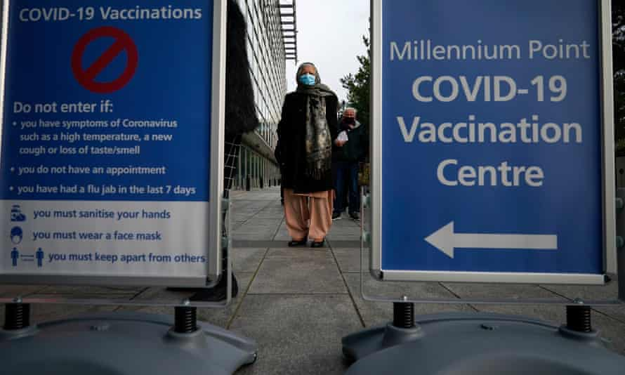 People queue outside an NHS Covid-19 vaccine centre in Birmingham