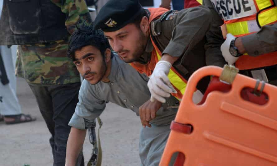 Pakistani volunteers rescue a student after the attack