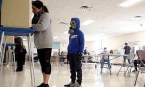 Kelly John fills out a ballot as her son Gunnar John, 8, stands behind her wearing a gas mask inside a polling station at Douglas High School during the presidential primary election, held amid the coronavirus outbreak, in Milwaukee.