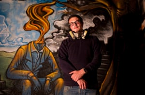 Souza poses in front of a piece he painted on a wall of his home