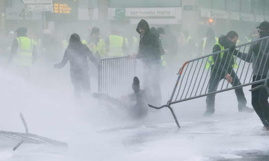Police use water spray to disperse protesters wearing yellow vests in Brussels, Belgium.