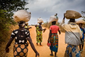 Women carrying sacks of maize on their heads