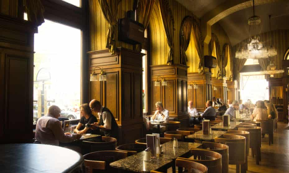 Rows of marble-topped tables with round-backed wooden chairs, huge windows with alcove seating, wood panelling, high ceilings and sun streaming in giving golden lighting to the interior of Café Schwarzenberg, Austria