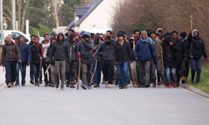 Migrants carry sticks during clashes near the ferry port in Calais on Thursday after at least five migrants were shot while queuing for food.