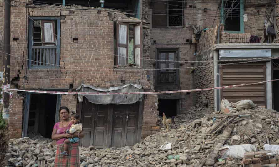 A woman carrying a child stands in front of damaged buildings in Patan, Nepal