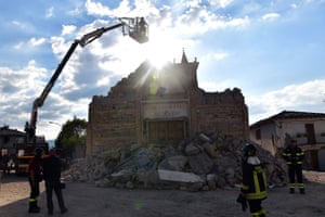 A member of the emergency services is lowered into a church to retrieve artefacts in San Lorenzo a Flaviano, Italy