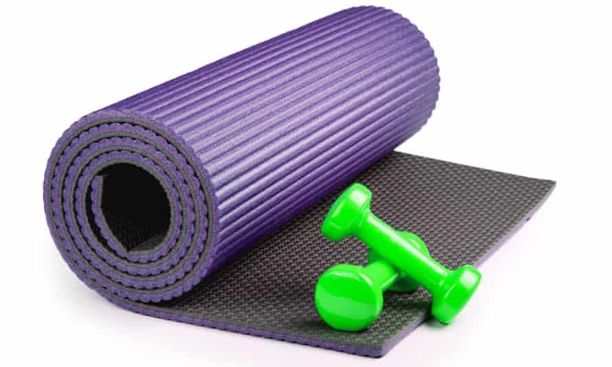 Yoga mat with dumbbells isolated on white background.