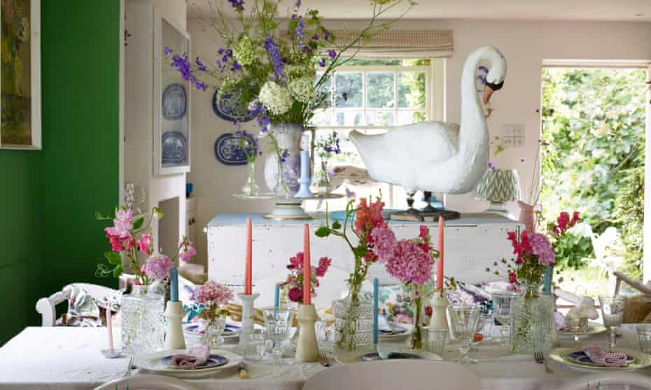 A set table with flowers and candles, a large model of a swan behind and dark green paint on the walls