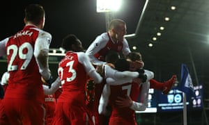 Arsenal players celebrate with Alexis Sánchez after his free kick deflected in off West Brom's James McClean.