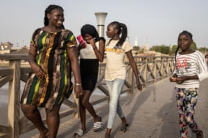 Girls walk along a bridge from the island of Fadiouth