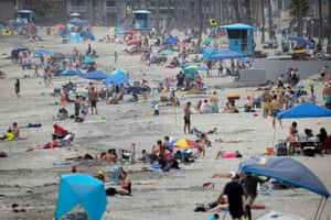 Few people wear masks as they gather at the beach in Oceanside last week.
