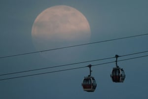 The supermoon rises above the Emirates Air Line cable car in London, Britain.
