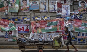 Campaign posters are seen along a street in Quezon city, Philippines, ahead of midterm elections seen as a referendum on Rodrigo Duterte's drug war.