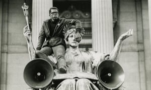 A protester in the 1968 protests at Columbia sits on the shoulder of a statue