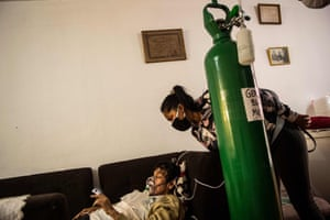 Callao, Peru: German Blanco's daughter, July, checks on her father as he lies on a couch at home after contracting coronavirus