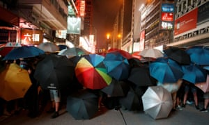 Protesters hold umbrellas as they face riot police after a march in Hong Kong's tourism district on 7 July.