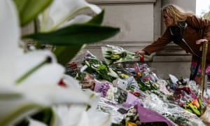 Members of the public lay flowers on the steps of the French embassy in London.