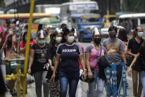 Commuters wear face masks and shields to help prevent the spread of the coronavirus as they walk along a busy street in Manila, Philippines on Friday, 19 March, 2021.
