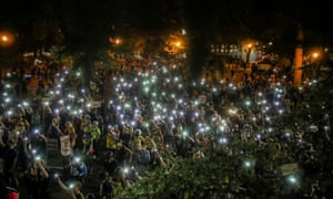 People shine cellphone flashlights during a demonstration against racial inequality and police violence in Portland, Oregon Wednesday.