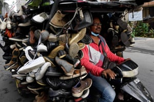 Phnom Penh, Cambodia A man rides a motorcart loaded with secondhand shoes for sale