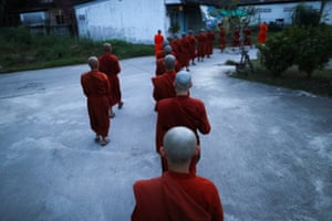 Novice monks go to receive food offerings from people at the Songdhammakalyani monastery
