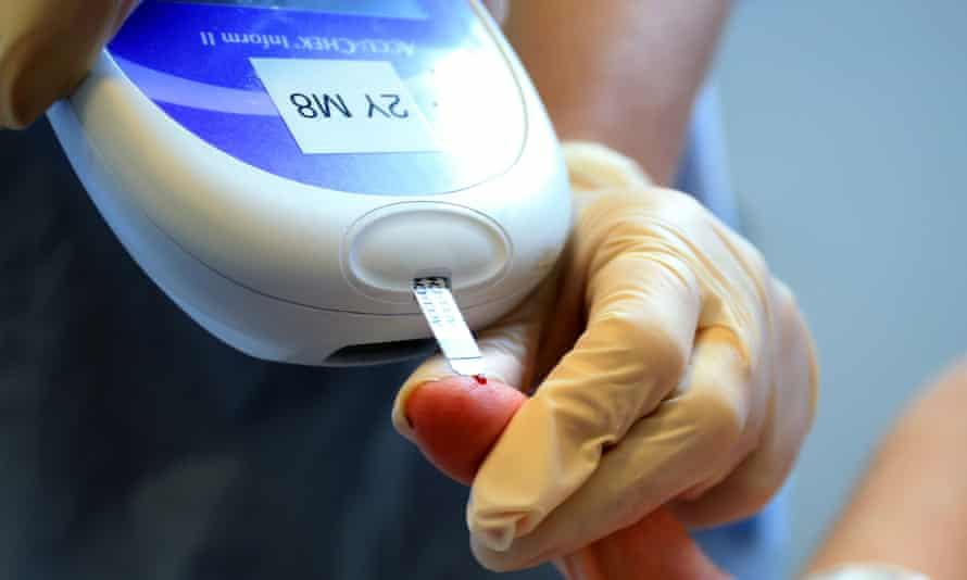 A nurse giving a patient a diabetes test.