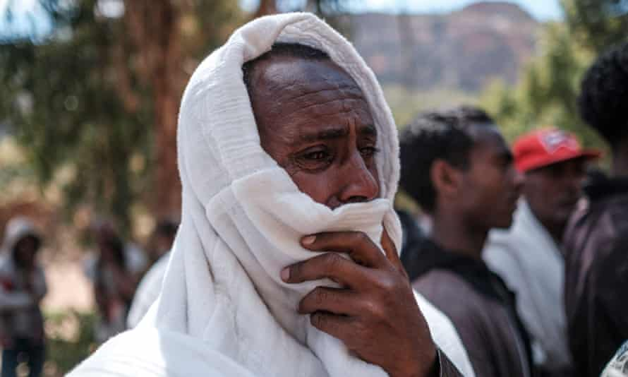 A man mourns the victims of a massacre allegedly perpetrated by Eritrean soldiers in the village of Dengolat