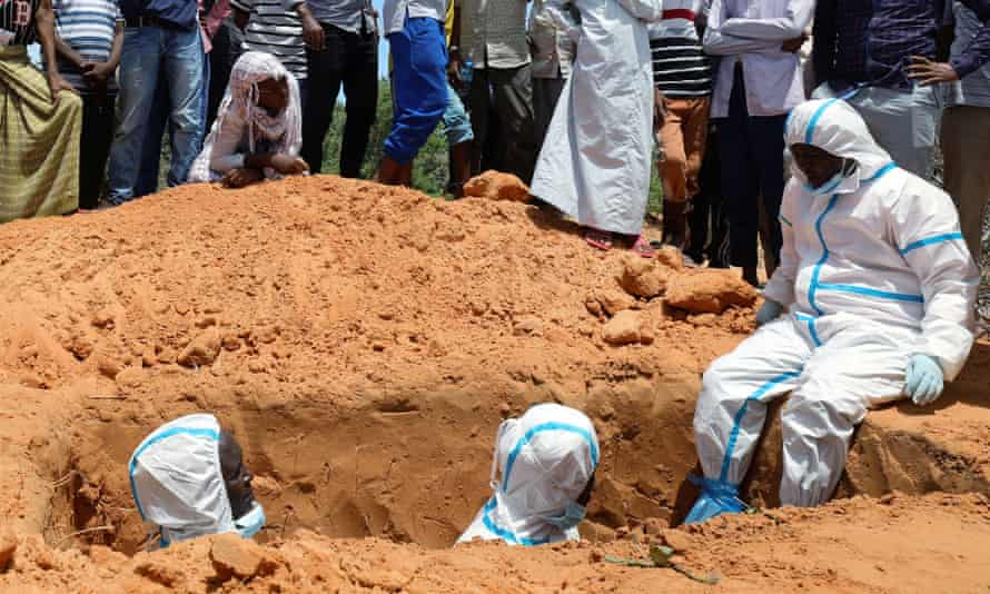 Somali workers in protective suits stand inside a grave in Mogadishu.