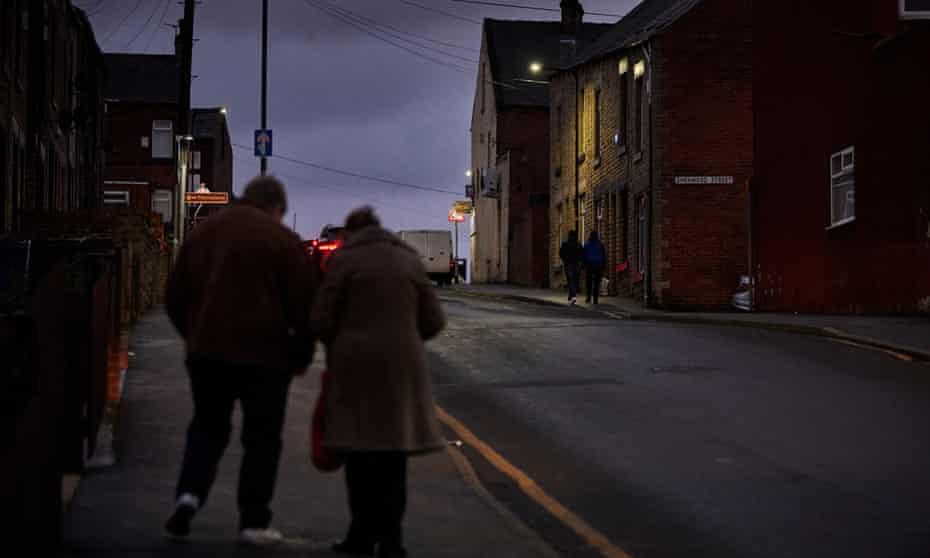 People walking down a street in fading light