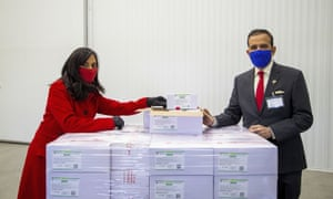 Anita Anand, left, Canada's Minister of Public Services and Procurement and the High Commissioner of India to Canada Ajay Bisaria pose with some of the first 500,000 of the two million AstraZeneca vaccine doses that Canada has secured through a deal with the Serum Institute of India.