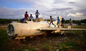 Children play on a destroyed fighter plane in Juba