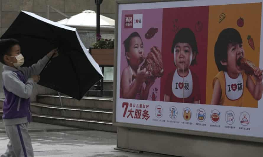 A child opens an umbrella near an advertisement for a restaurant featuring young children in Beijing on Monday.