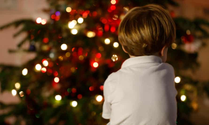 A child sits next to a Christmas tree - vulnerable young people face increased risk of neglect or abuse over the holiday period.