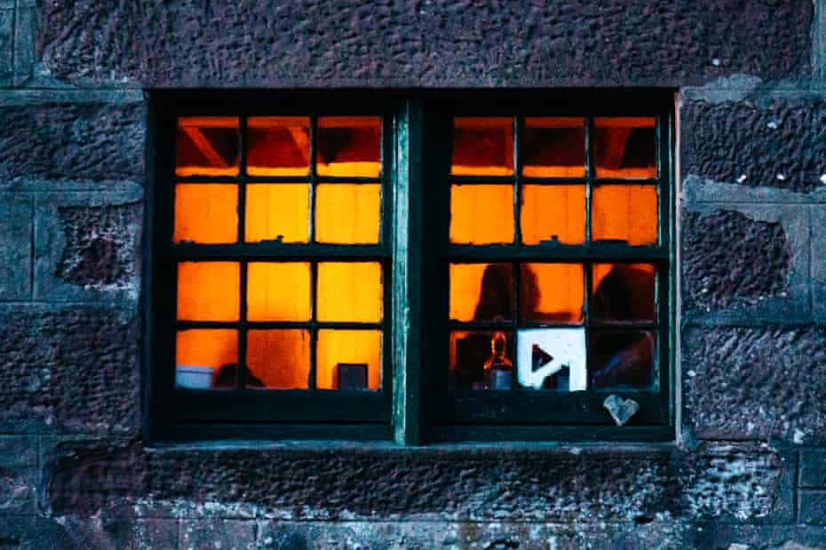 Seen from outside, a bothy window glows with the light of a fire.