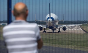 A man watches an Airbus A300-600ST prepare to take off from its factory in Wales
