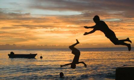 Tuvaluan children leaping into the sea on Funafuti atol Tuvalu at sunset